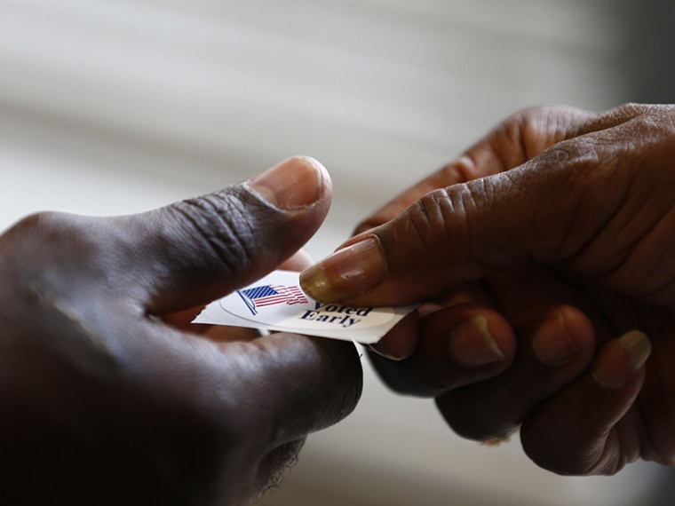 A poll worker hands a sticker to a voter at a polling place in Charlotte, North Carolina October 27, 2012. (Photo by Chris Keane/Reuters)