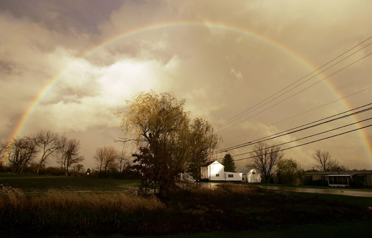 A rainbow is seen arching over a farm house in Dover, Pa. (Photo by Carolyn Kaster/AP)