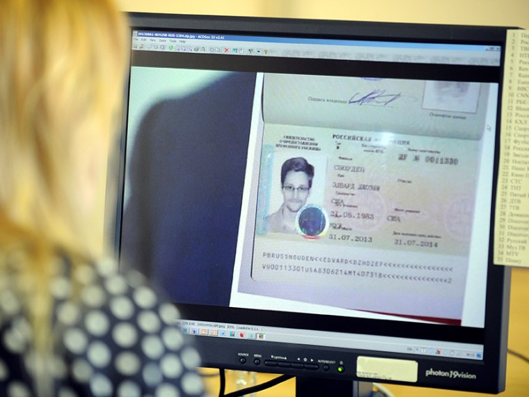 A woman watches a footage on her computer, showing  the lawyer of fugitive US intelligence leaker Edward Snowden holding his client's one year's asylum permit at Sheremetyevo airport in Moscow on August 1, 2013. (Photo by Stringer/AFP/Getty)