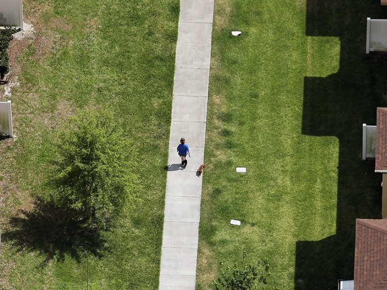 A woman walks her dog along the walkway area behind 1231 Twin Trees Lane where slain teenager Trayvon Martin's body was found after he was killed by George Michael Zimmerman, inside the Retreat at Twin Lakes community, on April 13, 2012 in Sanford,...