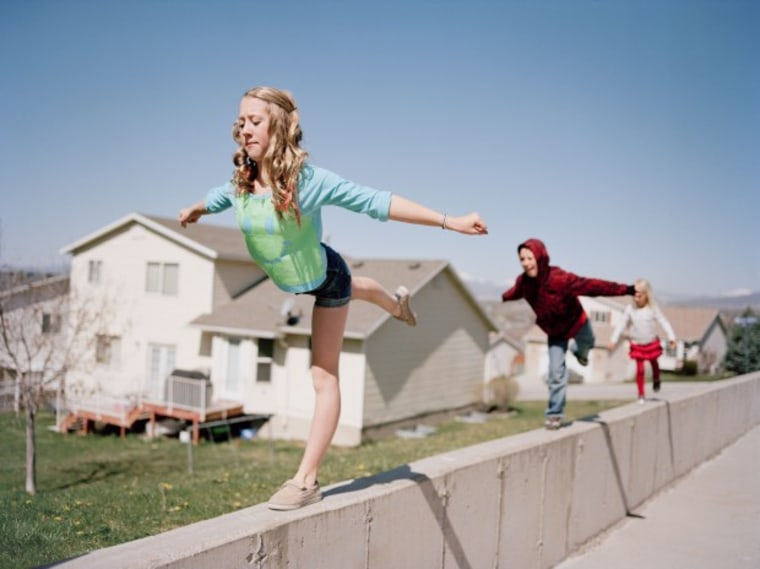 A young teeanage girl does gymnastics moves while balancing on a concrete ledge as her little brother and sister copy her with a view of mountains and her family's suburban neighborhood in background. Pleasant Grove, Utah. Brian Shumway/Redux