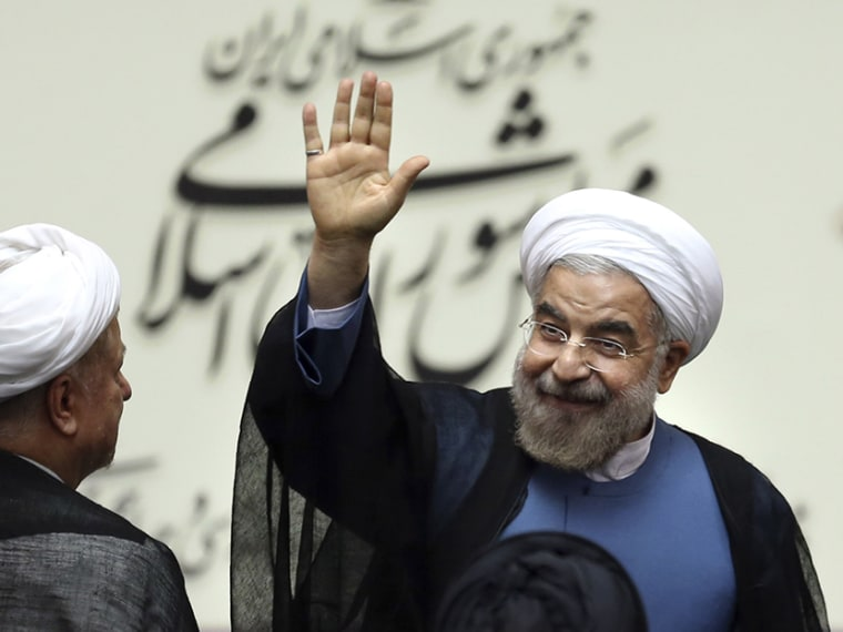 Iran's new President Hasan Rouhani, waves after swearing in at the parliament, in Tehran, Iran, Sunday, Aug. 4, 2013.  (Photo by Ebrahim Noroozi/AP)