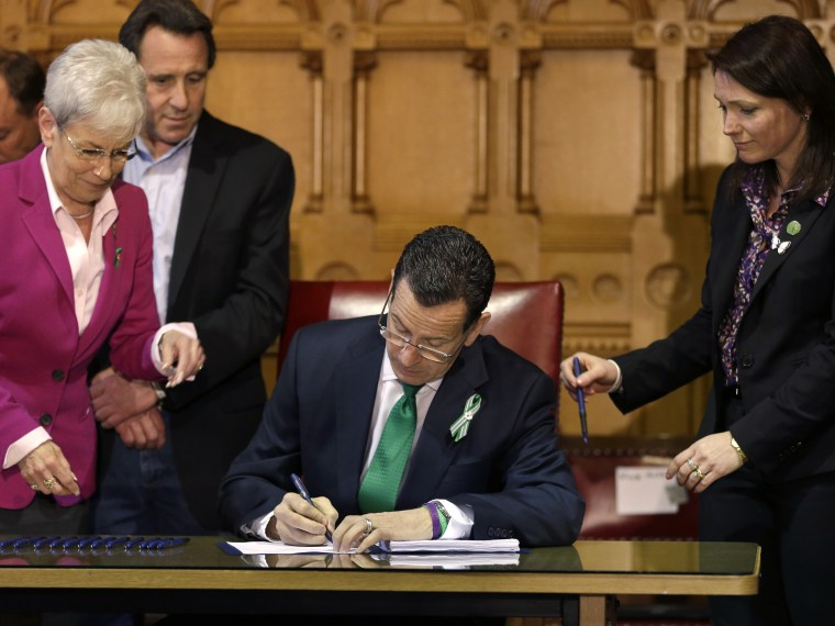 Connecticut Gov. Dannel Malloy signs new legislation at the Capitol in Hartford, Conn. on April 4, 2013, that includes new restrictions on weapons and large capacity ammunition magazines, a response to last year's deadly school shooting in Newtown. ...
