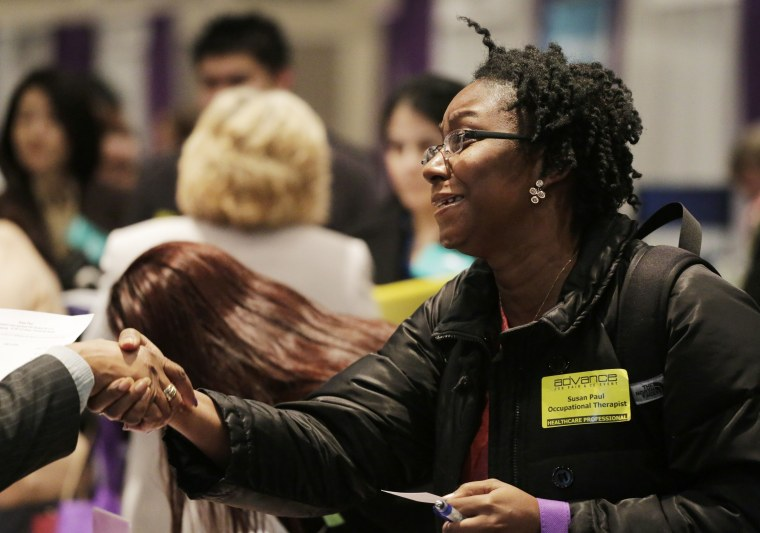 Susan Paul, who has recently completed a Masters program in occupational therapy, shakes hands with a recruiter at a healthcare job fair, Thursday, March 14, 2013, in New York.   (Photo by Mark Lennihan/AP)