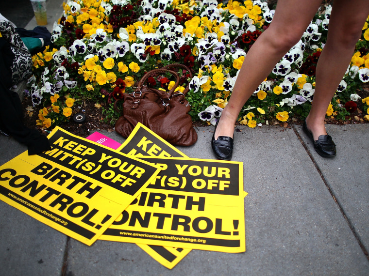 File Photo: A women participates in a protest outside of the Hyatt Regency where Republican presidential candidate, former Massachusetts Gov. Mitt Romney was scheduled to attend a fundraiser on March 22, 2012 in Washington, DC. (Photo by Mark Wilson...