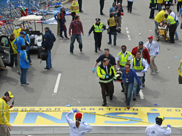 Medical workers wheel the injured across the finish line during the 2013 Boston Marathon following an explosion in Boston, Monday, April 15, 2013. (Photo by Charles Krupa/AP Photo)