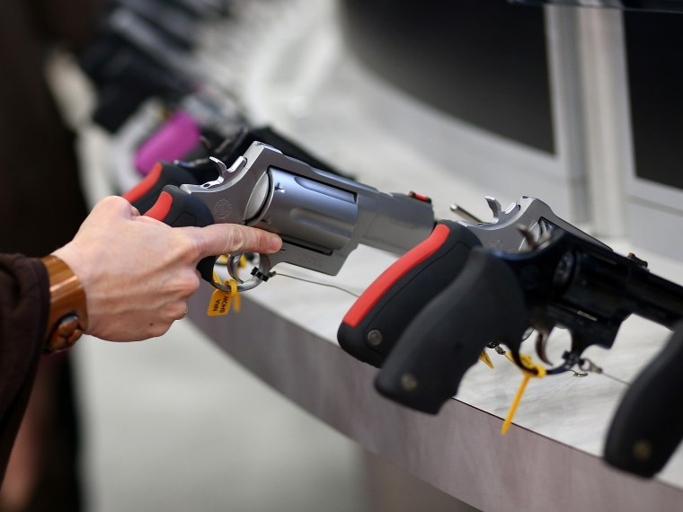 An attendee inspects a handgun during the 2013 NRA Annual Meeting and Exhibits at the George R. Brown Convention Center on May 3, 2013 in Houston, Texas. (Photo by Justin Sullivan/Getty Images)