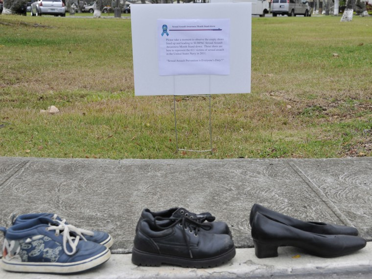 A Friday April 6, 2012 photo provided by the US Navy shows a sign that is displayed describing the 611 pairs of shoes lining the sidewalk in front of Sharkey Theater before a sexual assault event at Joint Base Pearl Harbor-Hickam in Hawaii. The shoes...