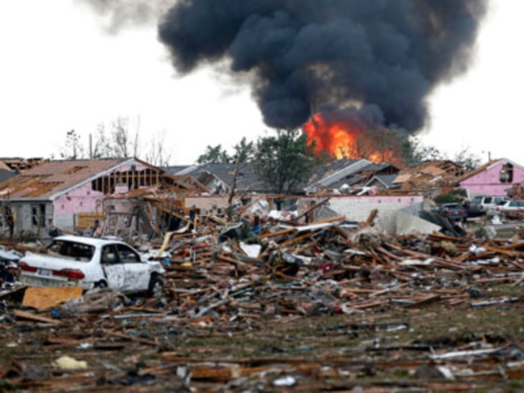 A scene of fire and destruction in Moore, Oklahoma after a tornado ripped through the area on May 20, 2013. (Photo by Sue Ogrocki/AP)