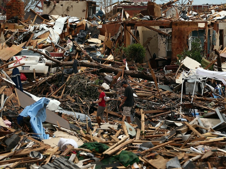 Two volunteers search through the rubble of a neighborhood on May 23, 2013 in Moore, Oklahoma. U.S. President Barack Obama promised federal aid to supplement state and local recovery efforts.  (Photo by Tom Pennington/Getty Images)