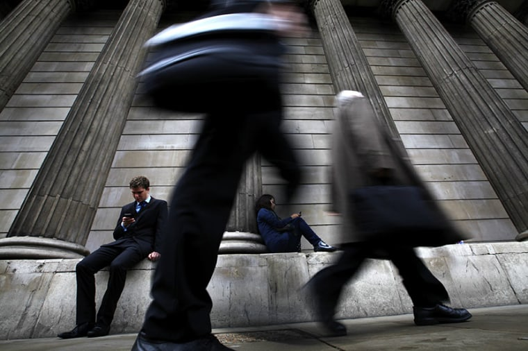 A man and woman use their mobile phones as commuters walk past the columns of the Bank of England in the City of London, July 3, 2012.  (Photo by Andrew Winning/Reuters)