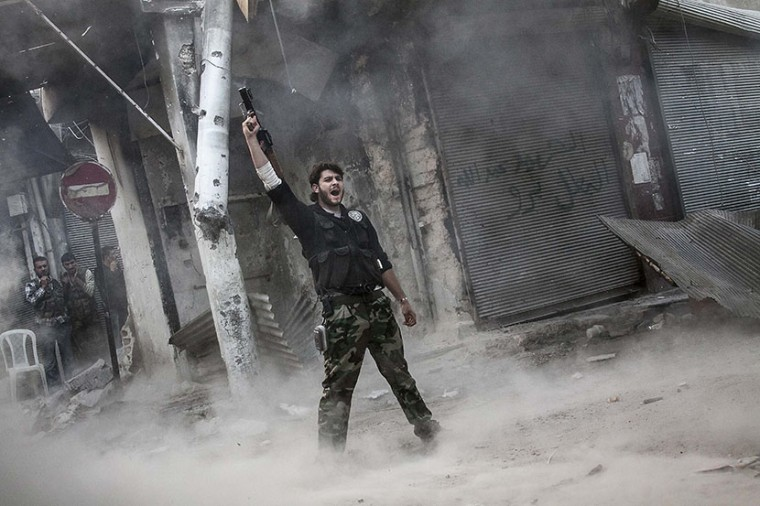A rebel fighter claims for victory after he fires a shoulder-fired missile toward a building where Syrian troops loyal to President Bashar Assad are hiding while they attempt to gain terrain against the rebels during heavy clashes in the Jedida...
