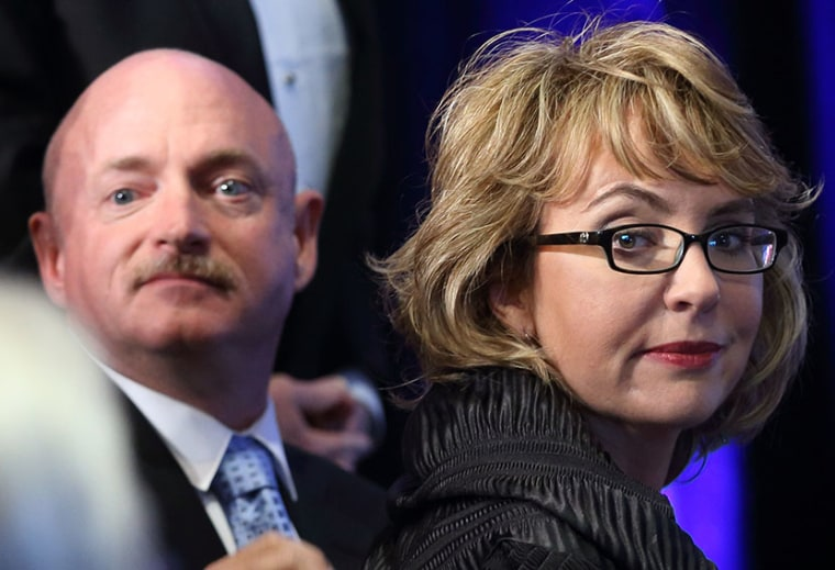 Former Arizona congresswoman Gabrielle Giffords, right, and her husband Capt. Mark Kelly look back at the crowd after arriving at a ceremony awarding Giffords the John F. Kennedy Profile in Courage Award at the JFK Library in Boston, Sunday, May 5,...