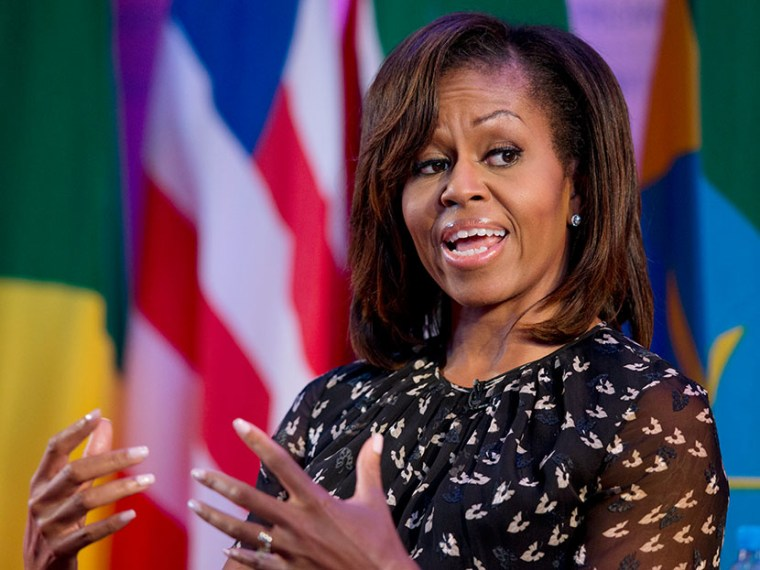 """U.S. first lady Michelle Obama gestures as she speaks during African First Ladies Summit: """"Investing in Women: Strengthening Africa,"""" hosted by the George W. Bush Institute, Tuesday, July 2, 2013, in Dar es Salaam, Tanzania.  (Photo by Carolyn Kaster/AP)"""