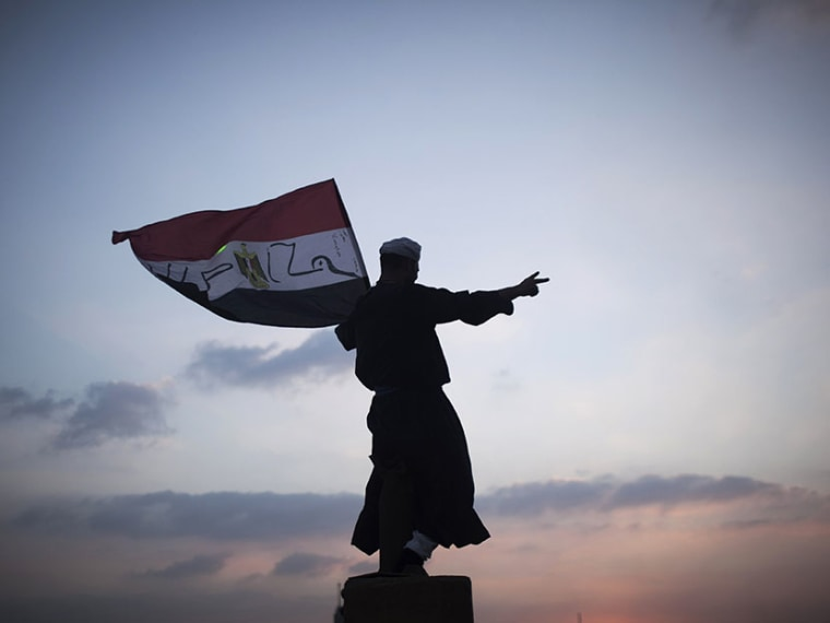 A Egyptian protester waves a national flag in Tahrir Square during a demonstration against Egypt's Islamist President Mohammed Morsi in Cairo, Monday, July 1, 2013.  (Photo by Manu Brabo/AP)