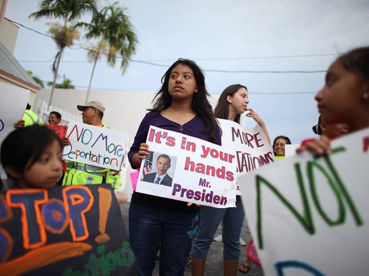 """Elena Marquez (C) holds a sign reading """"it's in your hands Mr. President"""" as she and others participate in a rally calling on the President Barack Obama to immediately suspend deportations and for Congress to pass an immigration reform that's inclusive..."""
