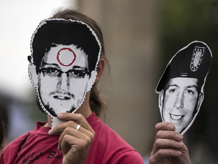 People hold portraits of former U.S. spy agency contractor Edward Snowden (L) and U.S. Army Private First Class Bradley Manning in front of their faces during a protest in front Brandenburg Gate in Berlin, July 4, 2013. (Photo by Thomas Peter/Reuters)