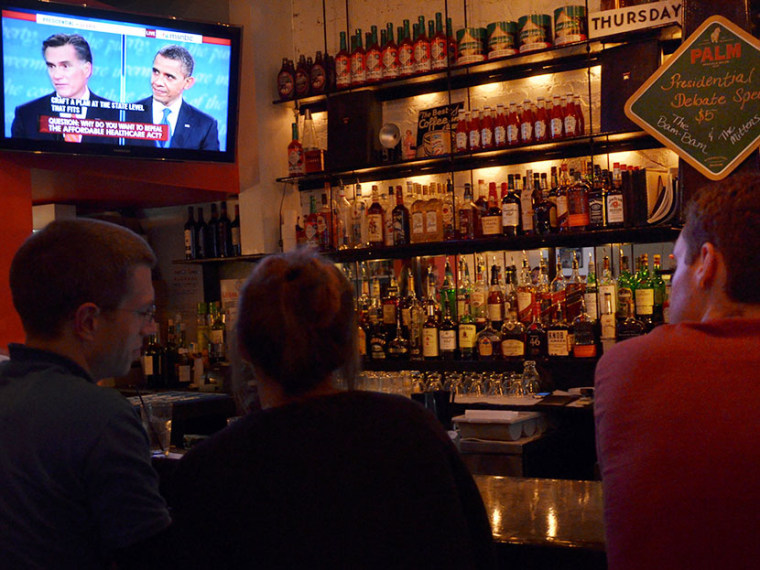 People watch television at a neighborhood bar hosting a presidential debate watching party in Washington, DC on October 3, 2012. (Photo by Eva Hambach/AFP/Getty Images)