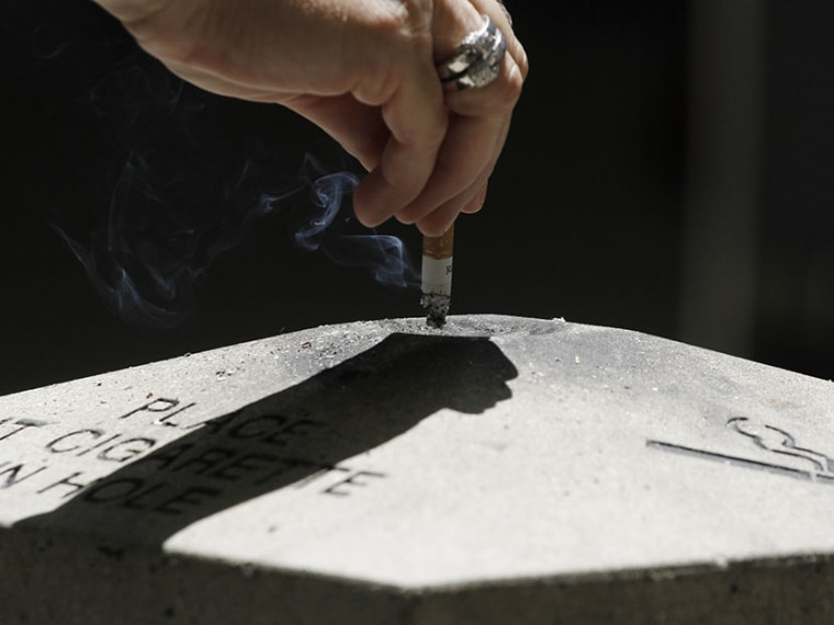 A woman disposes a cigarette in Los Angeles, California, May 31, 2012. (Photo by Jonathan Alcorn/Reuters)