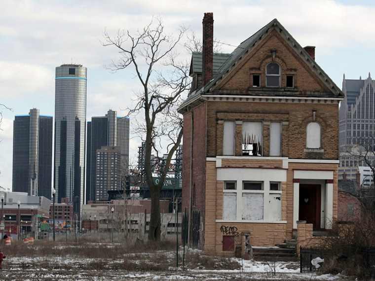 A vacant, boarded up house is seen in the once thriving Brush Park neighborhood with the downtown Detroit skyline behind it in Detroit, Michigan March 3, 2013. (Photo by Rebecca Cook/Reuters)