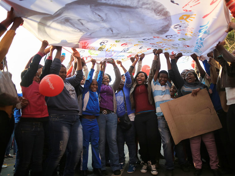 People dance and celebrate as they wave a banner of Nelson Mandela to celebrate his 95th birthday outside the Mediclinic Heart Hospital where he is being treated on July 18, 2013 in Pretoria, South Africa.   (Photo by Christopher Furlong/Getty Images)