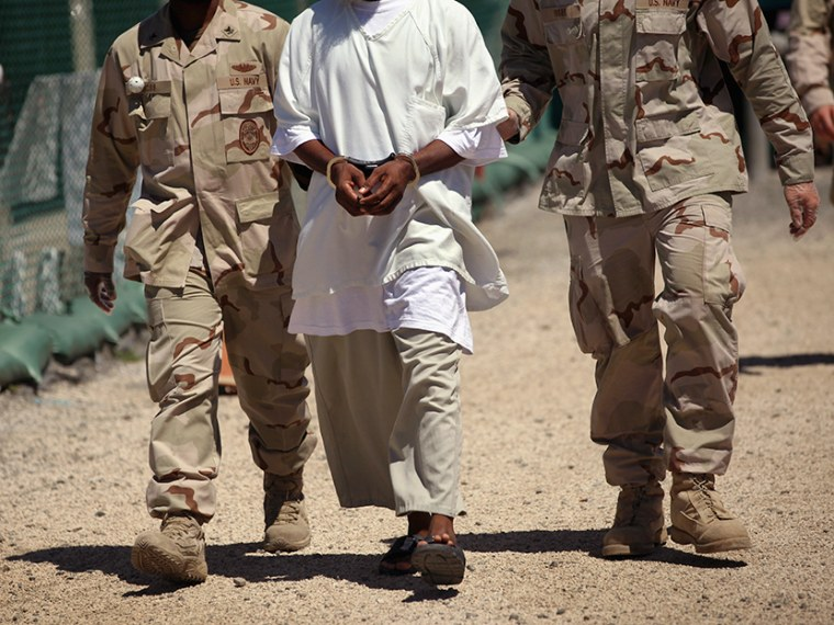 """U.S. military guards move a detainee inside the American detention center for """"enemy combatants"""" on September 16, 2010 in Guantanamo Bay, Cuba.  (Photo by John Moore/Getty Images)"""