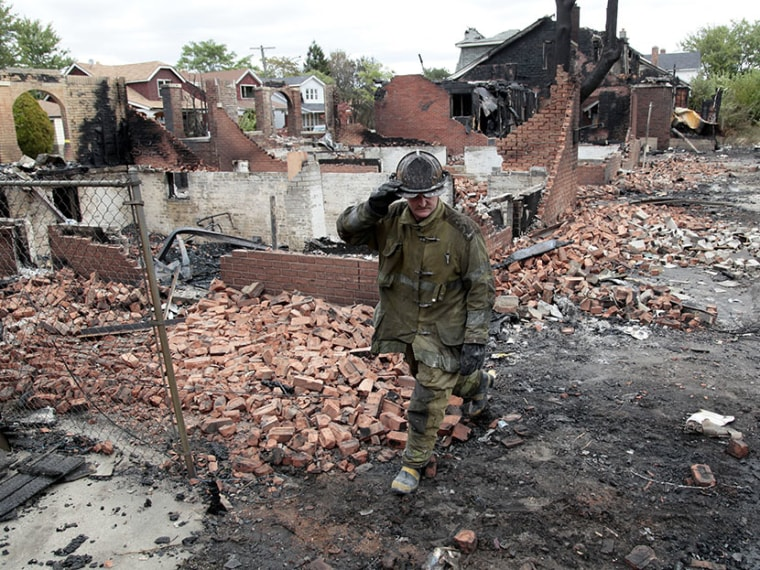 A Detroit fire fighter looks through the smoldering back yards of burned homes and garages on East Robinwood in Detroit, Michigan September 8, 2010.  Detroit's bankruptcy will likely fall hardest on  public sector employees.  (Photo by Rebecca Cook...