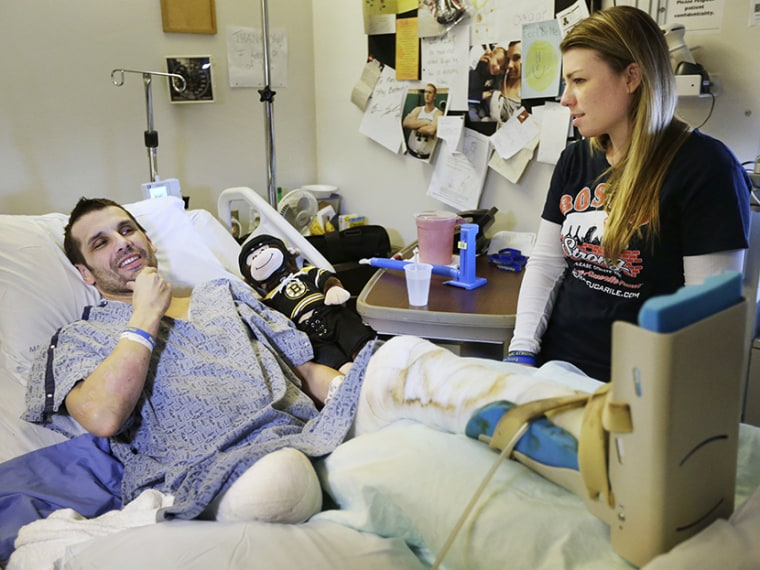 Marc Fucarile, left, speaks with members of the media as his fiancee, Jennifer Regan, right, looks on in his room at Massachusetts General Hospital in Boston on May 9, 2013.  (Photo by Steven Senne/AP)