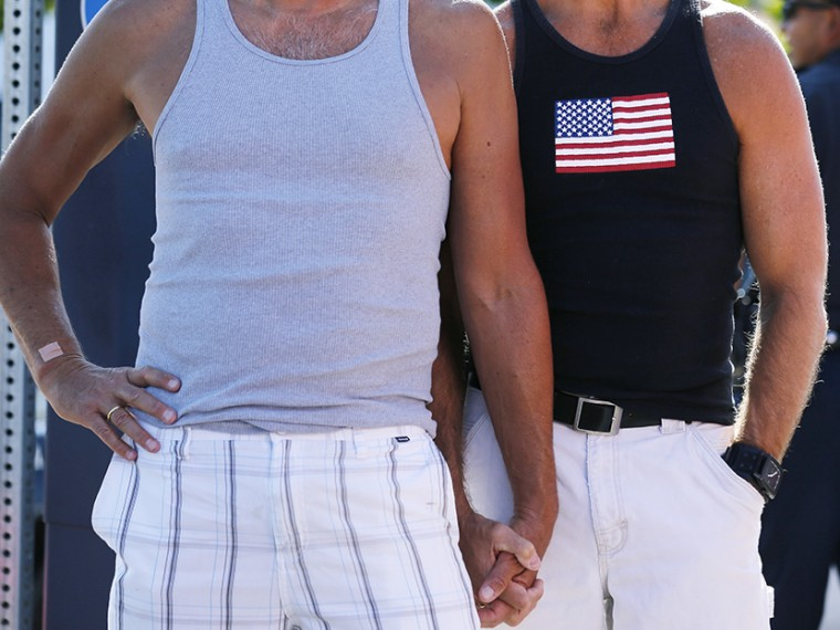 A gay couple holds hands as they attend a rally in support of the United States Supreme Court decision on marriage rights in San Diego, California June 26, 2013.  (Photo by Mike Blake/Reuters)