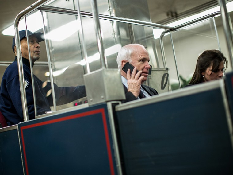 U.S. Sen. John McCain (R-AZ) (C) rides the Senate subway prior to votes on Capitol Hill March 22, 2013 in Washington, DC.  (Photo by Drew Angerer/Getty Images)