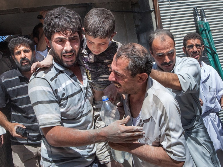 Syrian volunteers cry of joy after rescuing 8-year-old Mahmud Fayad who was trapped under the rubble of a destroyed house after a barrel bomb was dropped from an air force helicopter in Saraqeb in northwestern Syria on July 20, 2013.    (Photo by...