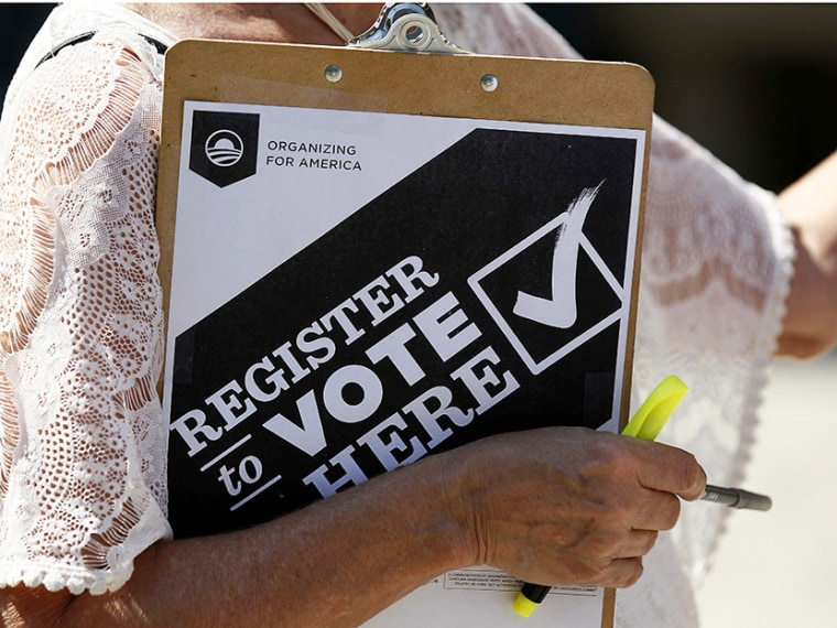Campaign volunteer Barbara Smalley-McMahan clutches her pad while attempting to register voters in downtown Raleigh, N.C., on Sept. 26, 2012. (Gerry Broome/AP)