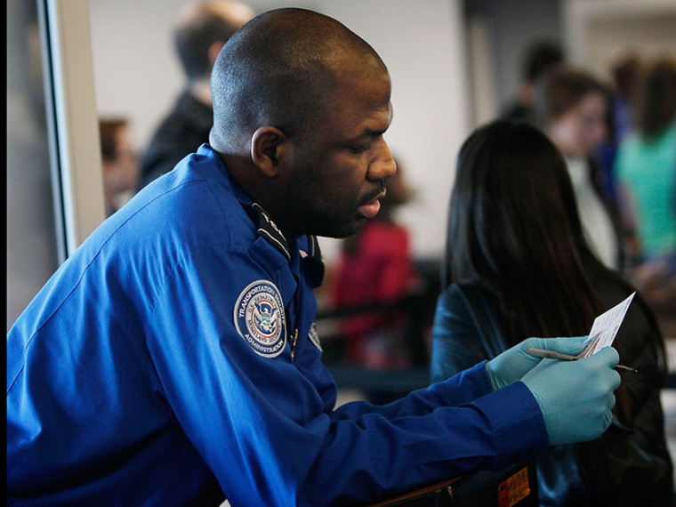 A Transportation Security Administration officer looks over the identification of a passenger during a security screening November 24, 2010 at LaGuardia airport in the Queens Borough of New York City.   (Photo by Chris Hondros/Getty Images)
