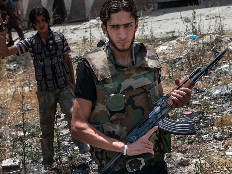 """Syrian rebel fighters belonging to the \""""Martyrs of Maaret al-Numan\"""" battalion leave their position after a range of shootings on June 13, 2013 in the northwestern town of Maaret al-Numan in front of the army base of Wadi Deif, down in the valley.  ..."""
