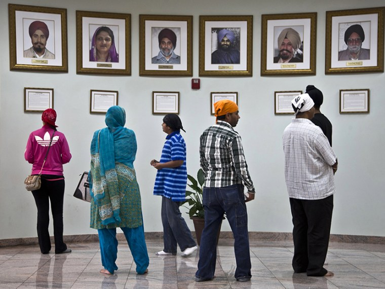 Visitors look at a memorial near the entrance of the Sikh Temple of Wisconsin Wednesday, July 31, 2013, in Oak Creek, Wis. Twelve months ago a white supremacist shot and killed six temple members, and the survivors plan to mark the one-year anniversary...