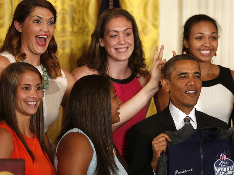Stefanie Dolson (top left), NCAA women's basketball 2013 national champions player from the University of Connecticut, puts bunny ears over U.S. President Barack Obama during a ceremony to honor the team in the East Room at the White House in...