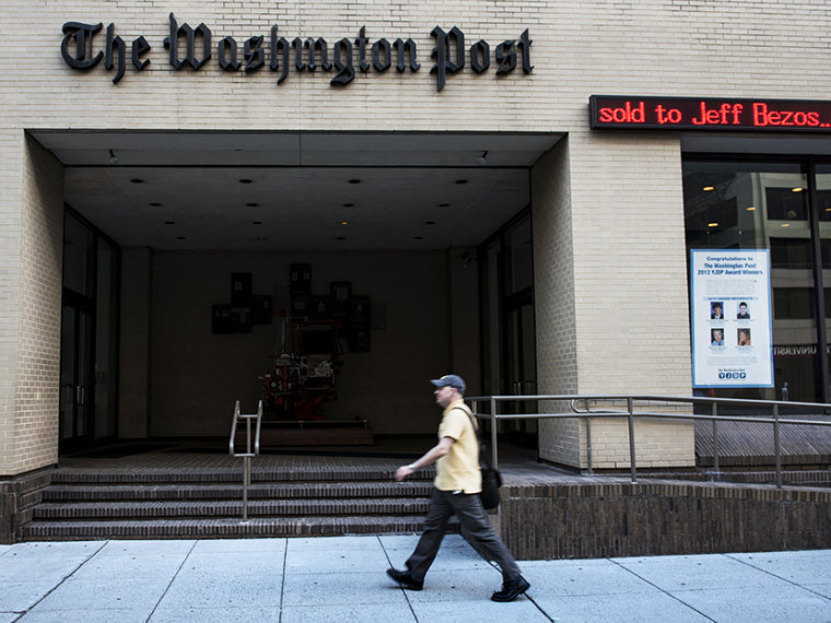 A man walks past The Washington Post building on August 5, 2013 in Washington, DC, after it was announced that Amazon.com founder and CEO Jeff Bezos had agreed to purchase the Post for USD 250 million. (Photo by Brendan Smialowski/AFP/Getty)