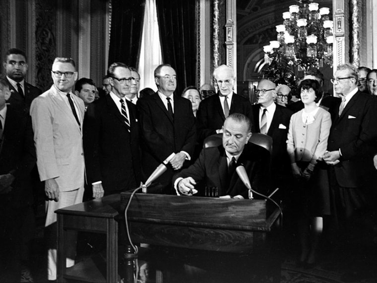 In this Aug. 6, 1965, photo, President Lyndon Baines Johnson signs the Voting Rights Act of 1965 in a ceremony in the President's Room near the Senate Chambers on Capitol Hill in Washington.   (Photo by AP)