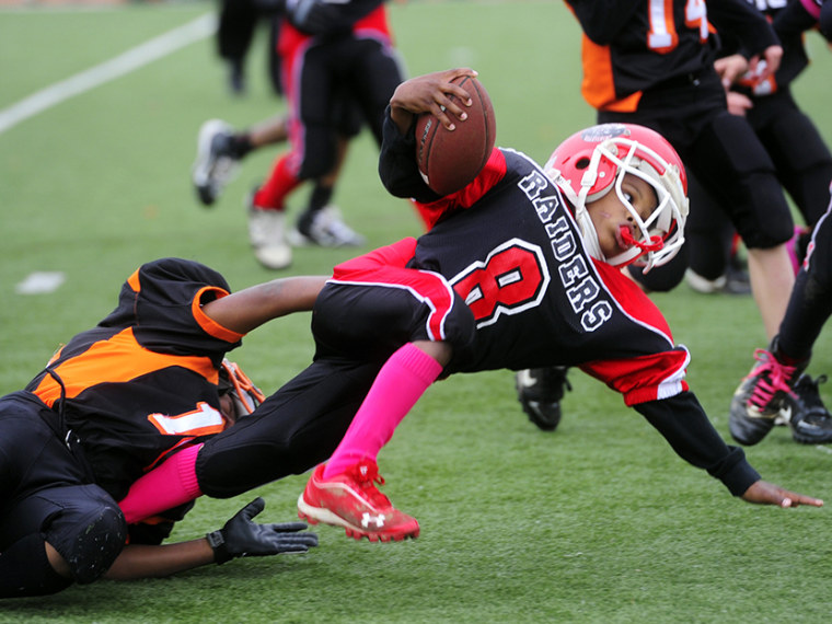 """Eastern York County's Isaiah Jones, 8, brings down Zamir Weedon-Parker, 8, in the second half of the rink varsity semifinal game at Central York High School on Oct. 28, 2012. Football had the highest concussion rate, according to the """"Game Changers""""..."""