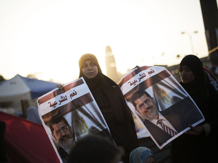 "A woman supporter of Egypt's ousted President Mohammed Morsi holds a banner of the former president  with Arabic that reads ""yes to legitimacy,"" during a protest near Cairo University in Giza, Egypt, Thursday, August, 1, 2013. (Photo by Manu Brabo/AP)"
