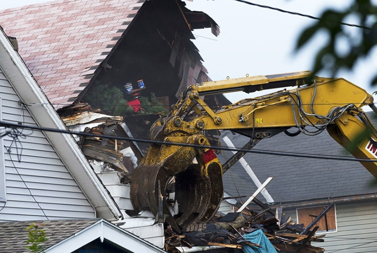A crane demolishes the home of Ariel Castro on August 7, 2013 in Cleveland, Ohio. Knight was abducted by Castro in 2002 and today the state of Ohio will demolish the home where she and two other women were held captive by Castro for over a decade. ...