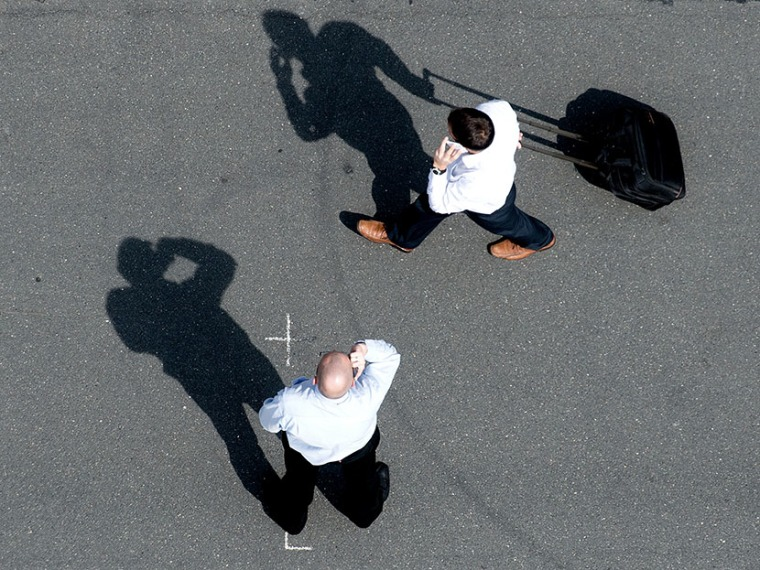 Two men make phone calls ontheir mobile phones at the exhibition grounds in Hanover, Germany, 08 May 2013. (Photo by Julian Stratenschulte/picture-alliance/DPA/AP)