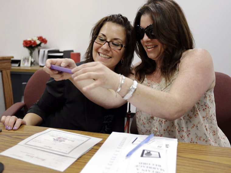 Tamara Davis and Nicola Cucinotta snap a photograph of their marriage license they obtained at a Montgomery County office despite a state law banning such unions, Wednesday, July 24, 2013, in Norristown, Pa.  Five same-sex couples have obtained...