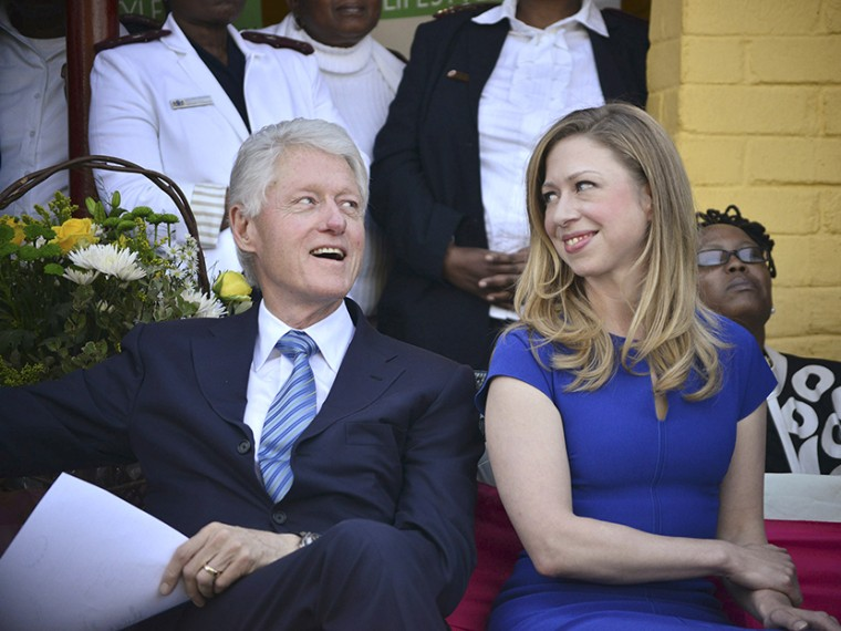 Former U.S. President Bill Clinton and his daughter Chelsea sit during their visit to the Ramotsa Clinic in Hammanskraal, near Pretoria, August 7, 2013. (Photo by Mujahid Safodien/Reuters)
