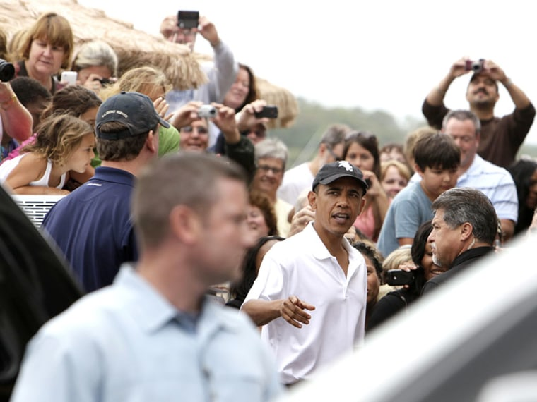 President Barack Obama turns to  greet people gathered outside Nancy's Restaurant in Oak Bluffs, Mass., while the first family is vacationing on Martha's Vineyard, Wednesday, Aug. 25, 2010. (Photo by Carolyn Kaster/AP)