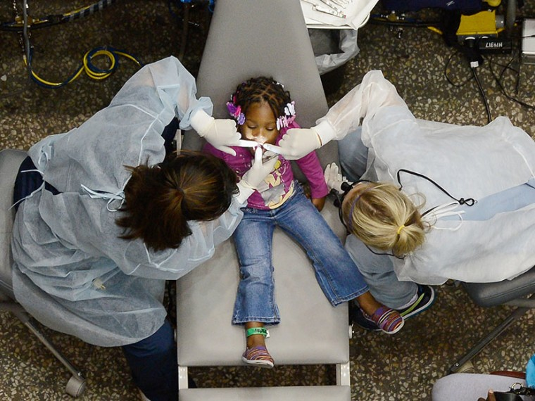 Kamora Cyprian, 2, gets her teeth cleaned as part of a free health care service for the uninsured at the Care Harbor clinic at the Los Angeles Sports Arena on September 27, 2012 in Los Angeles, California. (Photo by Kevork Djansezian/Getty Images)