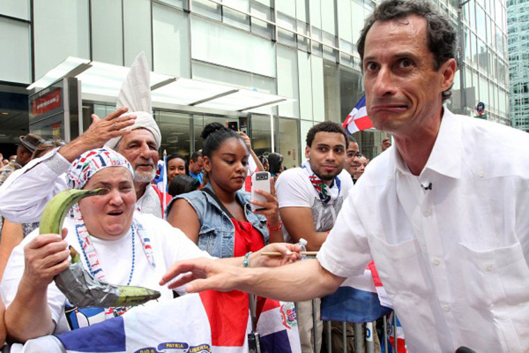 Anthony Weiner, running in the New York Mayors race, right, reacts after sharing a moment with a spectator and her plantains, left, as he takes part in the Dominican Day Parade on New York's Avenue of the Americas Sunday Aug. 11, 2013.  (Photo by Tina...