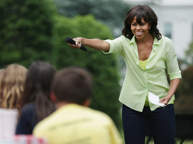 First lady Michelle Obama speaks to school children before they harvest the summer crop from the White House Kitchen Garden at the White House on May 28, 2013 in Washington, DC. (Photo by Chip Somodevilla/Getty Images)