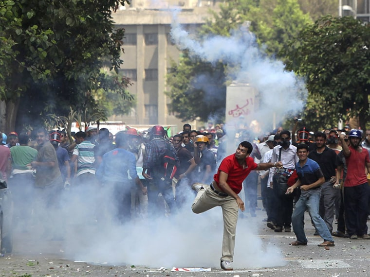 A supporter of ousted President Mohamed Mursi throws a tear gas canister back towards the police during clashes in central Cairo August 13, 2013. (Photo by Asmaa Waguih/Reuters)