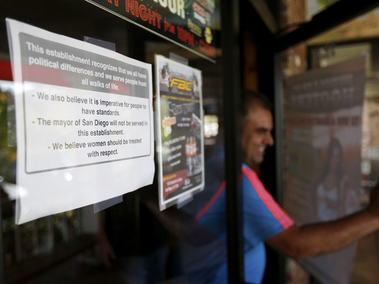 A man passes a sign, left,  posted on the outside of the entrance to a Hooters restaurant stating that San Diego Mayor Bob Filner will not be served Tuesday, Aug. 13, 2013, in San Diego. (Photo by Gregory Bull/AP)